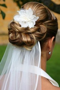 Bride's under veil with loose looped chignon bun and flower bridal hair ideas…