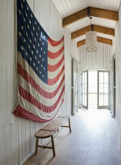 A vintage American flag draped in a rustic, beamed hallway