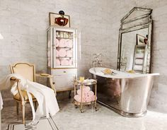 "Gleaming silver tones enhance this guest bath's old-world elegance. Designer Betty Lou Phillips chose a luxurious French-inspired theme for the decor. She paid attention to details like the tub and its floor-mounted water filler, the 19th-century crystal chandelier, the freestanding nickel-leg washstands, the vintage glass pharmacy chest, and fittings that read chaud and froid. ""They give the room character, a period feel. They're functional, too, of course. That's another French trait…"