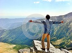 A man standing on a mountain top with arms outstretched, embracing life and adventure.