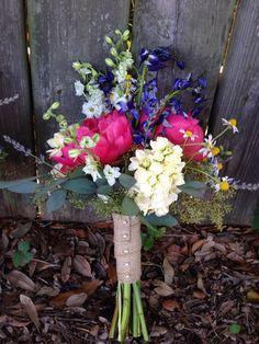 Wild flower bouquet of coral peonies, yellow stock, blue delphinium