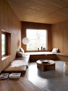 Villa Weinberg, Aarhus, Denmark, wood lined den with built in benches, concrete floors, sheepskin throw on bench