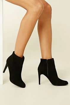 A pair of faux suede ankle booties featuring a zip side, a stiletto heel, and a slightly pointed toe.