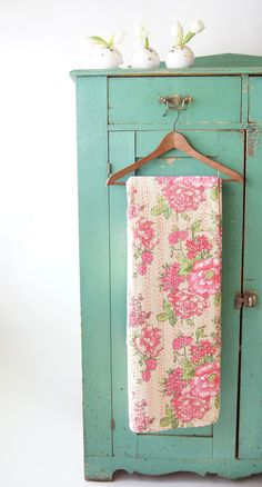 Turquoise vintage cabinet and a floral quilt