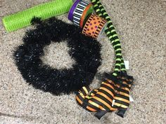 Make you front door ready for the Halloween season with this simple and festive witch hat wreath with dangling legs. The kids will love it. Lay out your suppli…
