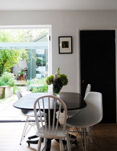 white eames chairs with dark table and other white chairs