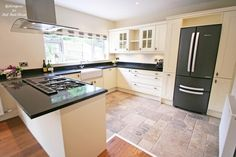 Eastbourne : Large English country kitchen with black granite worktop, island cooking area, cream shaker doors, double Belfast sink, American fridge freezer and roman blind