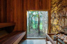 Revestida por madeira e pedra, o destaque da sauna é o quadro fixo de alumínio e vidro, da Tecnofeal, posicionado estrategicamente a fim de criar a sensação de que o usuário está em plena mata. O projeto da residência é do escritório Reinach Mendonça Arquitetos Associados