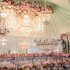 It's no secret that we have a soft spot for weddings that feature pink floral and this #reception is no different. The incredible pink floral halos encircling the crystal chandeliers create a cloud-like design that's simply heavenly #whitelilacinc | WedLuxe Magazine