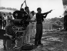 Godard tests the firepower of a revolver during the filming of 'Pierrot le Fou' (1965)