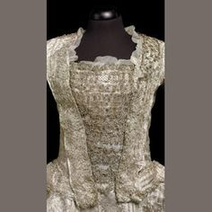 Bonhams. Court Mantua and petticoat of ivory silk, French c. 1770.  Elaborately brocaded with a pattern of narrow stripes and a vertical undulating ribbon of leaves and ears of corn alternating with floral sprays. Fitted bodice with structured pleating to the back, possibly formerly of open sack-back construction, having gathered self-fabric detailing later applied to waistline, possibly furbelows, with later silver lace trimmed stomacher. [More detail and much info on court dress at link.]