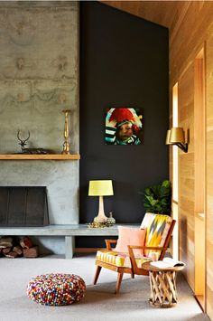 Emma O'Meara - desire to inspire - I love the dark wall color with the mix of the bright colors (picture, chair, pouf) and textures from the wood panel and concrete fire surround