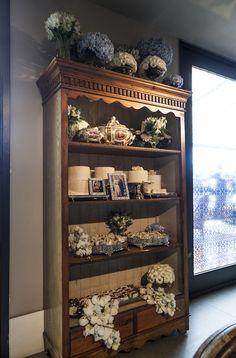 Decoração clássica para bodas de safira com detalhes em vitrais azuis e flores brancas. Estante em madeira com fotos, bolos e bem casados. Fotos: Douglas Daniel