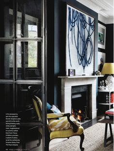 love the dark walls, citrine accents, and bold artwork