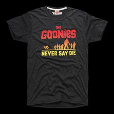 """From the truffle shuffle to the nefarious Fratellis, 1985's coming-of-age classic """"The Goonies"""" had it all and had us spending multiple summers on the hunt for our own One-Eyed Willie fortune. """"Goonies never say die!""""Pay homage to the Walsh bros, Chunk, Data, Mouth and the rest of the gang with this cinematic throwback.  • UNISEX STYLE• HEATHERED CHARCOAL, POLY/COTTON BLEND• CREWNECK TEE SHIRT• SLIMMER FIT• SOFT SCREENPRINT AT CHEST• MADE IN USA"""