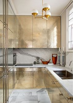 Marble is a beautiful contrast to chic gold cabinets. Check out more stunning kitchen backsplash ideas >> http://blog.diynetwork.com/maderemade/2015/08/11/kitchen-backsplash-ideas-2015/?soc=pinterest