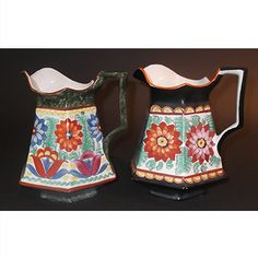 """These Mrazek Art Pottery pitchers display influences of """"Peasant Art"""" and Art Deco styles (see product description below for more information). The pair are identical in size and style, with slight variations in pattern and colour. One of them has a base colour of black with a strip of orange trim around the top rim, the other has a green sponge base with dark burgundy trim. Both are hand painted in a multi-coloured floral pattern around all of the six panels. The interior is in white…"""