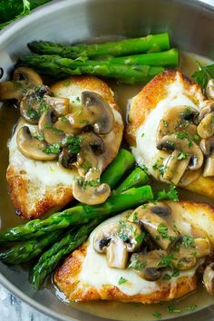Cooked chicken breasts in a stainless steel pan, topped with melted cheese and mushroom sauce.