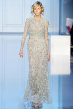 A diaphanous long-sleeved slim gown, in an icy gray-blue tulle draped and gathered at the waist and accented with metallic silver | Elie Saab Fall 2011 Couture #captivating