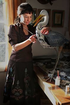 Aimée Baldwin works on a blue heron with feathers crafted from old-style European crepe paper in her studio.