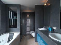 un carrelage gris et deux vasques blanches intégrées dans la salle de bains