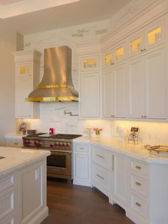 Street of Dreams Arizona - Via Annie Vincent Interiors - Elegant kitchen with white inset cabinets accented with brass hardware alongside white marble counters with ceiling height marble tiled backsplash.