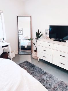 Instagram: @BLAIREWILSON Clean aesthetic bedroom. fresh, bedroom, white, minimal, plant, room makeover, full length mirror, area rug, tv, aesthetic, home, inspo, inspiration, goals, style, cozy, loft style, blaire wilson room, blaire wilson bedroom, all white, boho, modern, blogger, organized, tidy, urban outfitters, living spaces, home good, amazon
