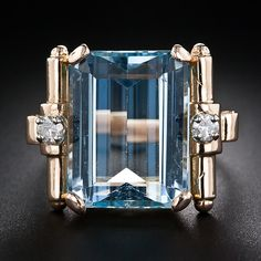 A serene and soothing pastel-blue aquamarine, weighing approximately 12.75 carats, is artfully presented between a pair of sparkling round diamonds set atop modernly stylized scroll motifs. The superbly modeled mounting is rendered in radiant 18 karat rose gold.