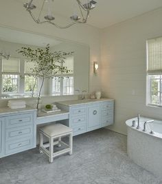 White and blue bathroom features a Choros Chandelier illuminating separate blue washstands topped with honed white marble under a large shared vanity mirror flanking a drop down make up vanity paired with an ivory nailhead stool.