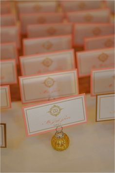 White, coral and gold escort cards ~ Photo: Jenna Christine Photography