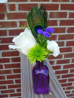 Few blooms with large peacock feather make this small centerpiece delicate, elegant and rustic all at the same time.