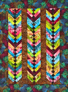Columns of bright prints stand out against darker prints for a dramatic quilt. Black squares in the centers of the columns give the columns a braided look.