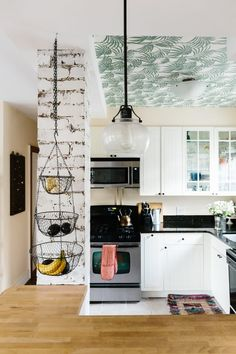 Audra loves greenery so much, they decided to wallpaper the kitchen ceiling with this bold Honolulu Palm Green pattern! See more of this tour: Adventurously Dreamy Home with a Touch of Golden Glam | Apartment Therapy