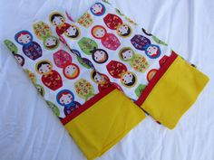 Matryoshka Dolls Abound on These Pillowcases!  Dolls in Bright Yellow, Red, Blue and Green on White Background Fabric, Trimmed in Red with Yellow Cuff  Hand Sewn Using Little Kukla Fabric Measures Approximately 21 X 31 (Standard Size) Made From New Materials Of Cotton Or Cotton Blend Fabric Pre-Washed To Prevent Shrinkage Machine Wash And Dry - Touch Up With Iron If Necessary Constructed With French Seams To Prevent Fraying Smoke And Pet Free Home  This Is Not A Licensed Product. Some may be…