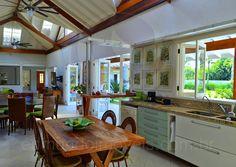 A espaçosa cozinha americana oferece um ar descontraído, típico do cenário praiano, e foi equipada com armários executados sob medida em madeira de lei e vidro, bancadas em granito bege e eletrodomésticos da linha branca.