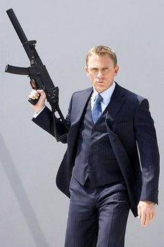 just waving around a rifle while wearing a three-piece. just another day at the office.