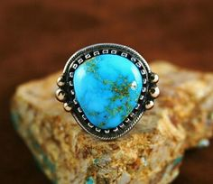 his exceptional one of a kind ring was hand made by award winning Navajo artist, Arland Ben. The turquoise of the piece is rare gem grade natural Darling Darlene from Nevada with an exquisite sky blue hue and eye-dazzling golden-brown matrix. This mine is no longer producing, and there is only a handful of this turquoise left, especially at this grade! With tremendous skill and precision the artist complimented the beauty of the stone with six large solid 14K gold droplets, Coral Turquoise, Turquoise Jewelry, Silver Jewelry, Southwest Jewelry, Southwest Style, Painted Desert, Blue Gem, Baubles And Beads, American Indian Jewelry