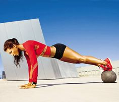 Rock a Cut-Out Dress With This Move: Hold a plank with feet on medicine ball, hands on ground (as shown). Keeping left foot on ball, bring right knee toward chest, then kick right leg out to side. Return to start; repeat on opposite side for 1 rep. Continue for 45 seconds. Rest 15 seconds. Works shoulders, arms, abs, obliques #SelfMagazine