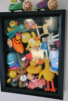 [Put your child's favorite old toys in a shadow box when they've outgrown them and hang it on the wall.]