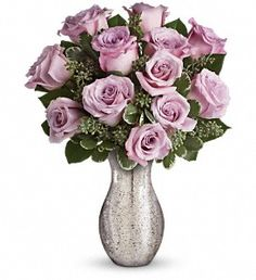 "Forever Mine ~ A sparkling mercury glass vase lends a feeling of vintage romance to one dozen delicate lavender roses. It's a bouquet as timeless as your love -and one she'll always remember!  Twelve lavish lavender roses are artfully accented with seeded eucalyptus and variegated pittosporum. Delivered in a silver mercury glass vase for a timeless look.  Approximately 12 1/2"" W x 16"" H  Orientation: All-Around  As Shown : TEV17-1A Deluxe : TEV17-1B Premium : TEV17-1C"
