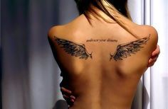 """Small Angel Wing tattoo on back with """"embrace your dreams"""" written in the center."""