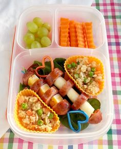 Sausage and cheese on skewers, Teriyaki fried rice, crinkle cut carrot slices and grapes.