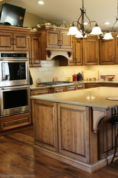 """Warm Birch wood stained with the """"Briarwood"""" finish and a black accent glaze added. Cambria #quartz #counters in the """"Walton"""" design and Walnut hardwood flooring.   VillageHomeStores.com"""