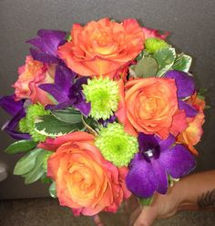 Vibrant bridesmaid bouquet to add color to any wedding. Made up of orange roses, purple dendrobium orchids, and lime green button mums. By Forget Me Not Flower Shop, North Haven, CT