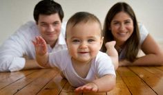 cute baby photo with mommy and daddy laying in the background.