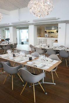 Eames eetkamerstoelen in warm grijs combineren mooi bij een licht houten tafel en helder witte muren
