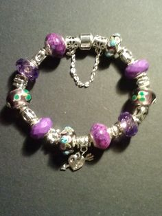 This is a sterling silver bracelet made with glass murano beads with different shades of purple and has silver spacers and a love heart charm with safety chain.