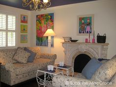 Loving the blue on the ceiling and pops of color on the wall & loveseats facing each other in front of fireplace.
