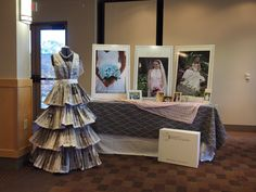 Simple booth for gown preservation company. Large posters. Newspaper wedding dress for attention.