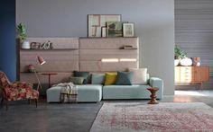 Set Collection-Living, design Studio Viganò. Il sistema di divani di forma semplice e rigorosa si integra alle pareti con pannellature tessili variamente attrezzabili. La boiserie imbottita, volendo trapuntata, permette di agganciare mensole, lampade e tasche portaoggetti.